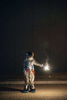 Spaceman standing on a road at night holding sparkler - VPIF00706