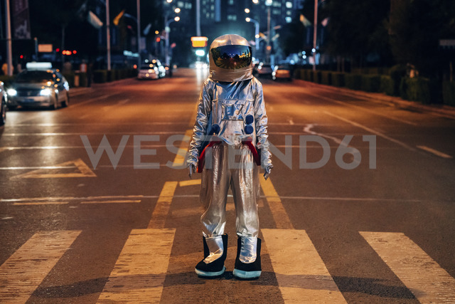 Spaceman standing on a street in the city at night - VPIF00709 - Vasily Pindyurin/Westend61