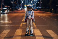 Spaceman standing on a street in the city at night - VPIF00709