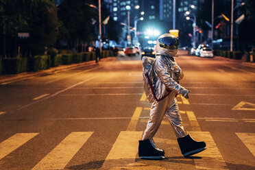 Spaceman walking on a street in the city at night - VPIF00715