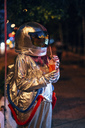 Spaceman in the city at night with takeaway drink - VPIF00718