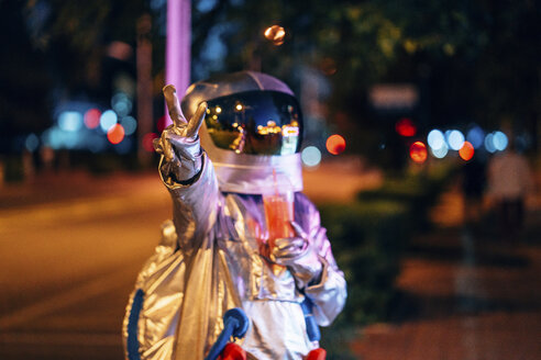 Spaceman in the city at night with takeaway drink making victory gesture - VPIF00721