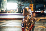 Spaceman on a street in the city at night attracted by shining projection screen - VPIF00727