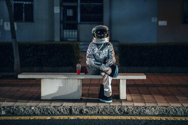 Spaceman sitting on bench at a bus stop at night with soft drink - VPIF00733