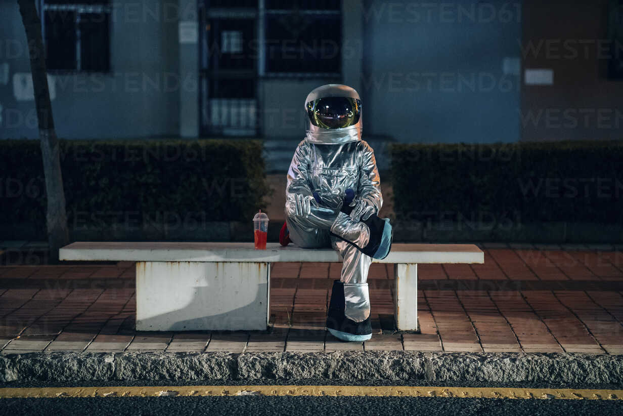 Spaceman sitting on bench at a bus stop at night with soft drink - VPIF00733 - Vasily Pindyurin/Westend61