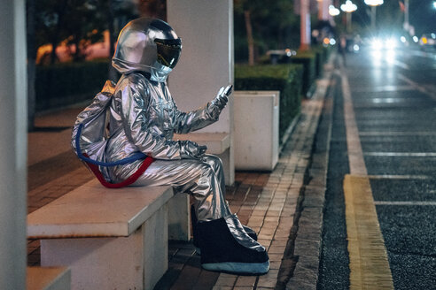 Spaceman sitting on bench at a bus stop at night holding cell phone - VPIF00736