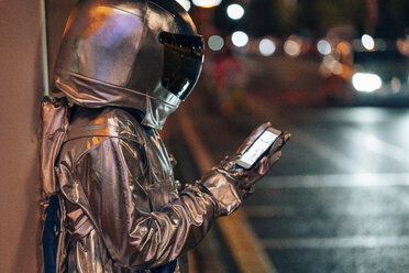 Spaceman at a city street at night using cell phone - VPIF00739