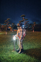 Spaceman standing at a lamp in a park at night - VPIF00742
