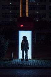 Spaceman standing at an illuminated box at night - VPIF00751