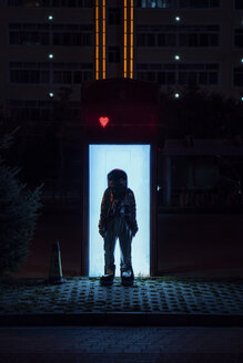 Spaceman standing at an illuminated box at night - VPIF00751