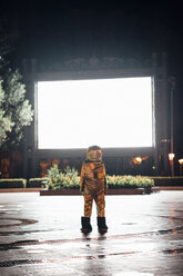 Spaceman on a square at night attracted by shining projection screen - VPIF00754