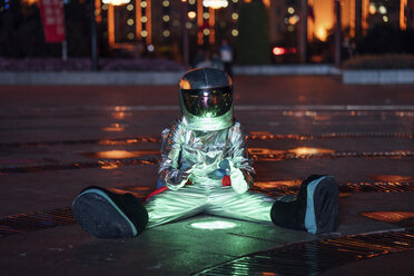 Spaceman sitting at a lamp on a city square at night warming his hands - VPIF00757