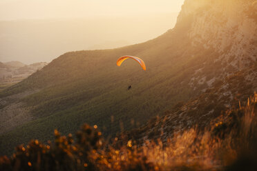 Spain, Silhouette of paraglider soaring high above the mountains at sunset - OCAF00348