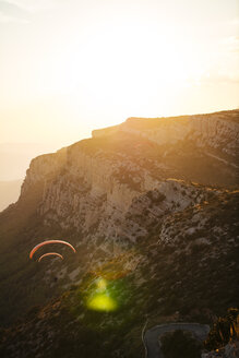 Spain, Silhouette of paraglider soaring high above the mountains at sunset - OCAF00351