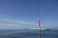 A woman tossing a paddle in the air on her SUP. - AURF04685