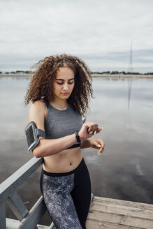 Young athletic woman at the riverside looking at wristwatch - VPIF00771