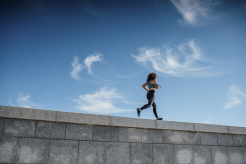 Young athletic woman running on a wall - VPIF00792