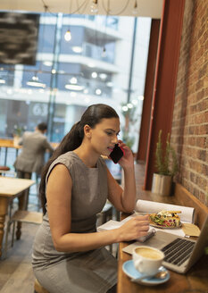 Businesswoman talking on smart phone, working at laptop in cafe - CAIF21981