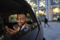 Businessman using smart phone in crowdsourced taxi at night - CAIF21993