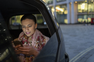 Businesswoman using smart phone in crowdsourced taxi at night - CAIF21999