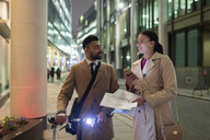Business people discussing paperwork on urban sidewalk at night - CAIF22008