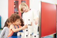 Teacher and curious students stacking large dominos in science center - CAIF22074
