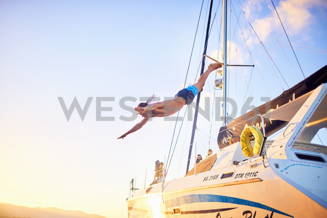 Young man diving off catamaran - CAIF22119 - Trevor Adeline/Westend61