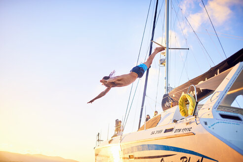 Young man diving off catamaran - CAIF22119