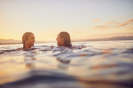Young couple swimming in ocean at sunset - CAIF22122