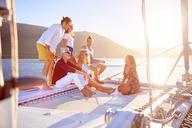 Friends relaxing on sunny catamaran - CAIF22131