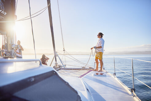 Young man holding rigging rope on sunny catamaran - CAIF22137