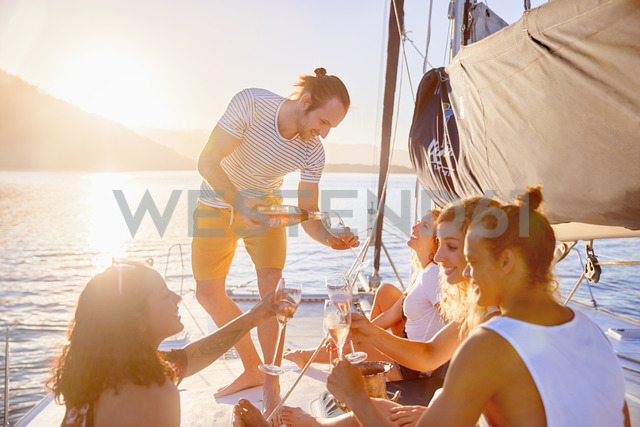 Friends drinking champagne on sunny catamaran - CAIF22146