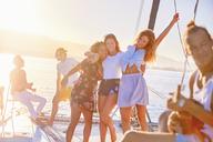 Playful women friends dancing on sunny catamaran - CAIF22152