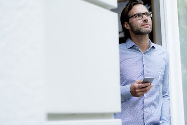 Confident man standing in doorframe holding cell phone - HHLMF00382