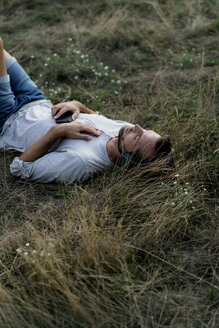 Relaxed man lying in field listening to music with headphones - HHLMF00385