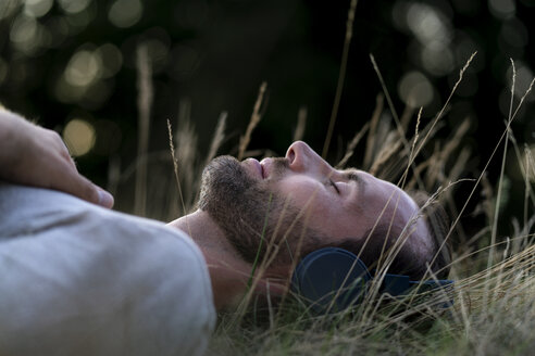 Relaxed man lying in field listening to music with headphones - HHLMF00388