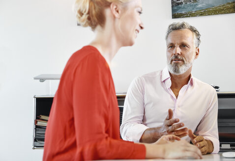 Two colleagues talking at desk in office - RHF02090