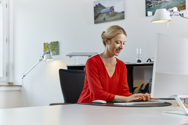 Smiling young woman working on computer at desk in office - RHF02111