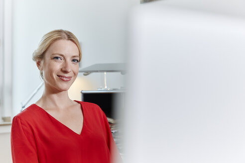 Portrait of smiling young woman in office - RHF02114