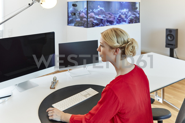 Young woman working on computer at desk in office - RHF02117