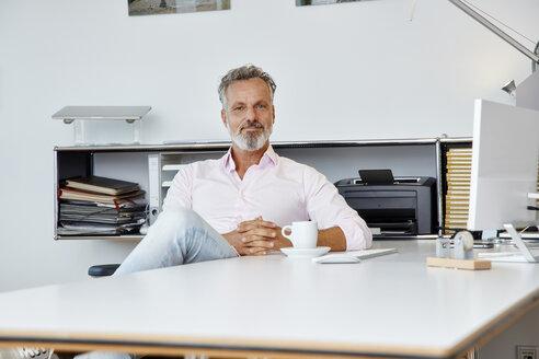 Portrait of confident businessman sitting at desk in office - RHF02132