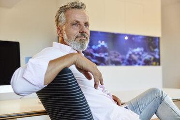 Businessman sitting in office thinking - RHF02135