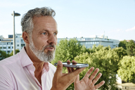 Portrait of mature man using smartphone outdoors - RHF02150