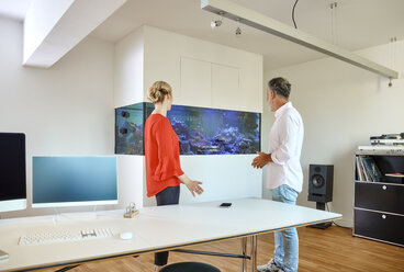 Mature man and young woman standing in office looking at aquarium - RHF02156