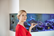 Young woman holding smartphone in office with an aquarium - RHF02159