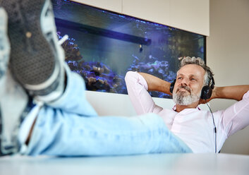 Relaxed mature man listening to music with headphones in front of aquarium - RHF02162