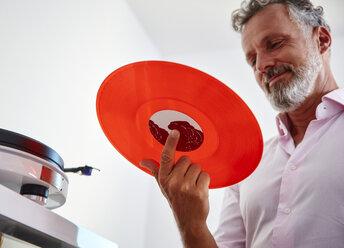 Smiling mature man holding red vinyl record - RHF02165