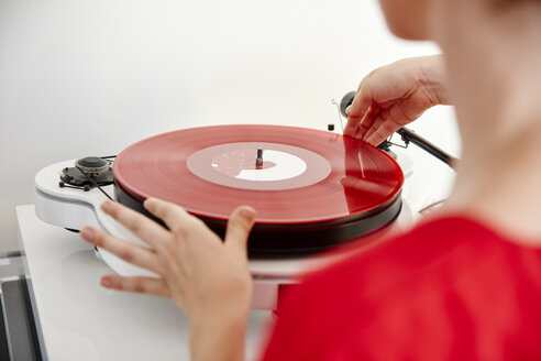Woman putting red vinyl record on record player - RHF02171