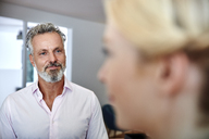 Smiling mature man looking at female colleague in office - RHF02177