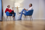 Mature man and young woman sitting in armchairs talking - RHF02183